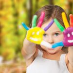 special needs child with fingers painted with a smiley face